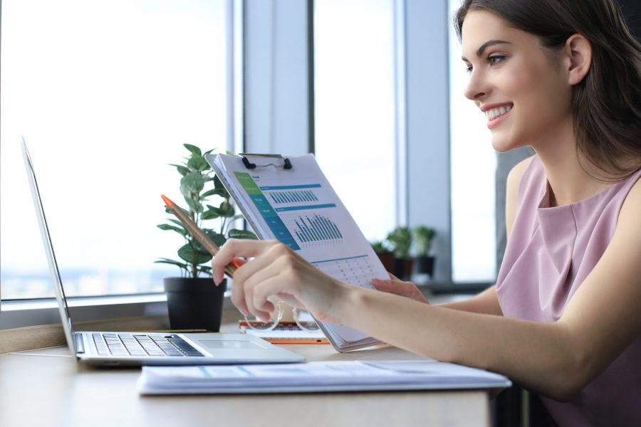 Beautiful young woman using laptop and looking at it while sitting at her working place